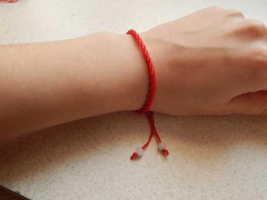 Шерстяная красная нить на запястье