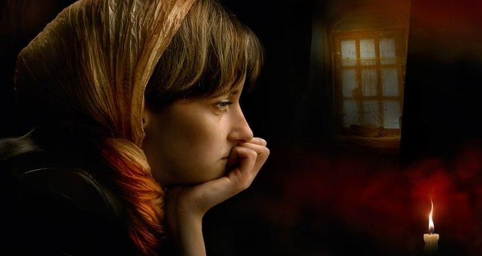 Девушка произносит заговор на свечу