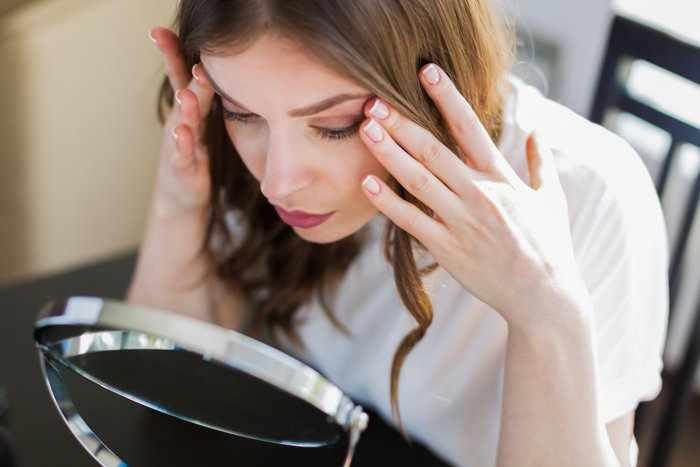 Женщина смотрит сосредоточено в зеркало