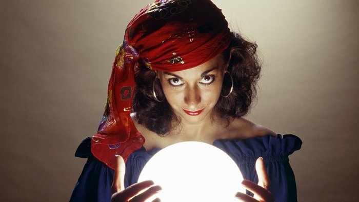 Ведьма читает заговор у хрустального шара