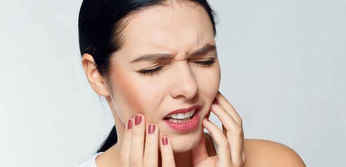 Женщина испытывает сильную боль в зубах