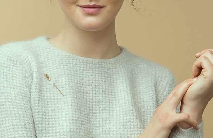 Девушка в свитере, которому приколота декоративная булавка