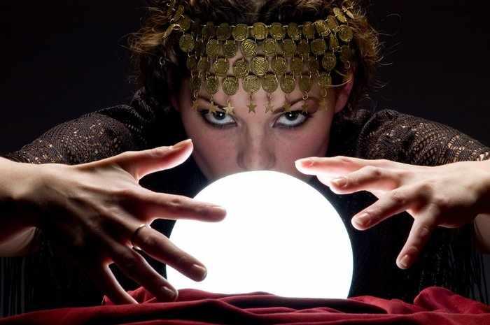 Ведьма читает заговор перед хрустальным шаром