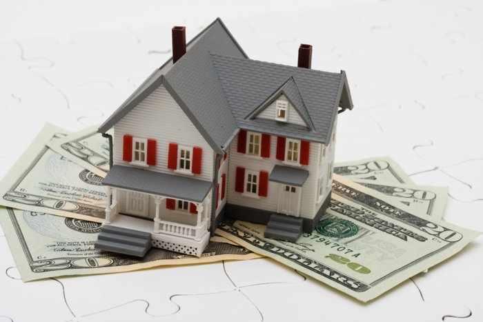 Макет дома и доллары - символы богатства